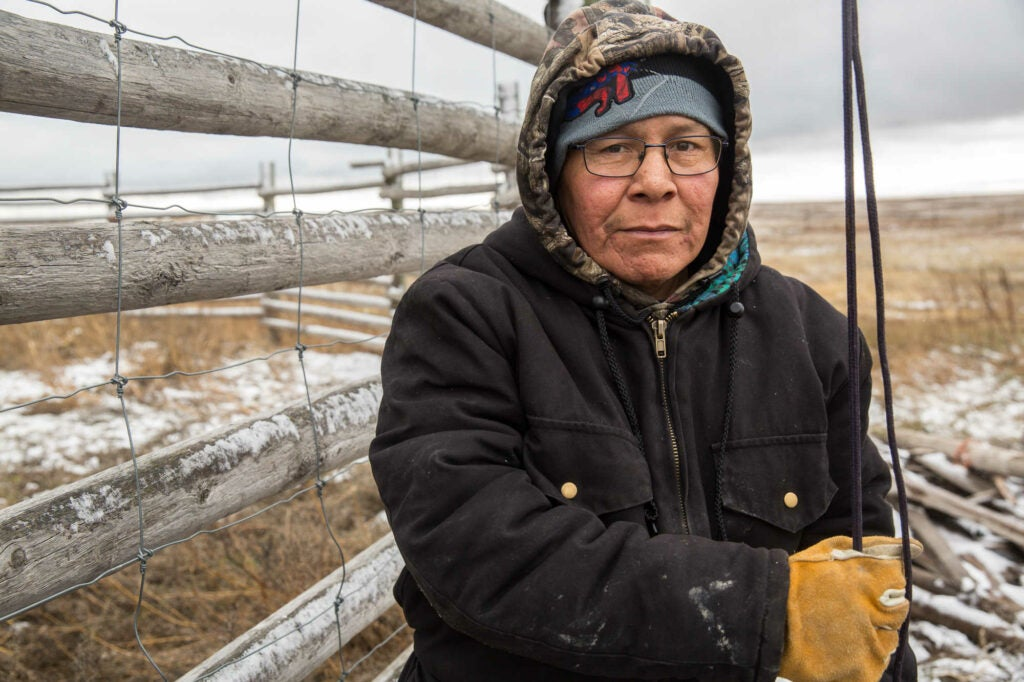 Bison rancher Man Black Plume standing in front of cattle fencing in a black jacket and work gloves