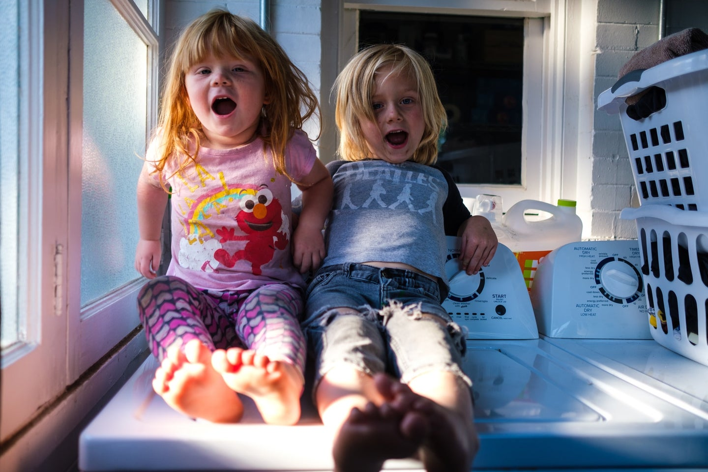 Two kids with blond and red hair sitting on a washer in a laundry room
