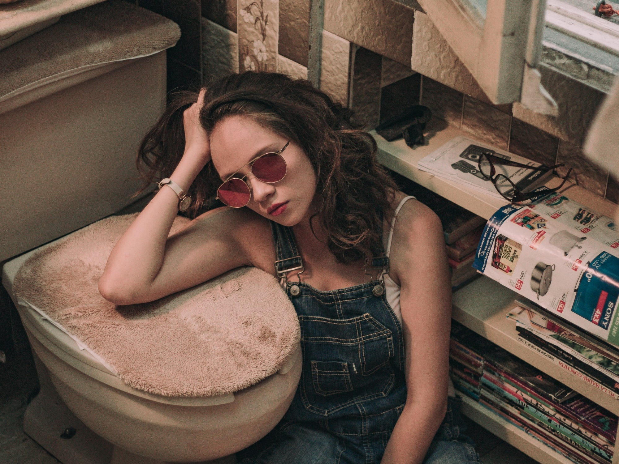 A frustrated woman sitting on the floor of a bathroom, resting her arm on the carpeted lid of a toilet.