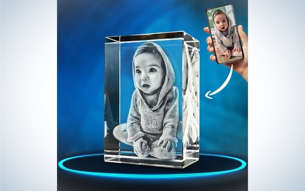 A photo reflected in a transparent glass box and with a photo of a small child inside.