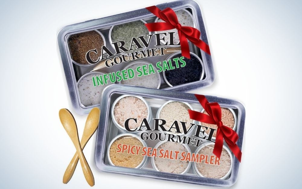 Two small boxes of silver color with six circular shapes inside you filled with different colors of sea salt and two wooden spoons of bamboo.