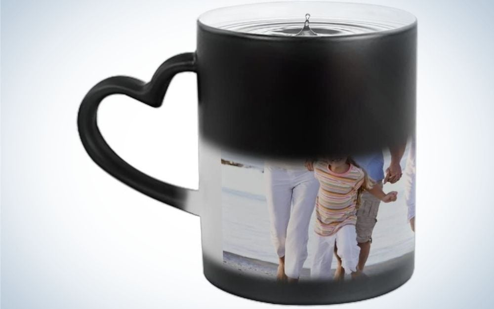 A black and white cup with a picture of a family printed on it and a heart-shaped tail in black.