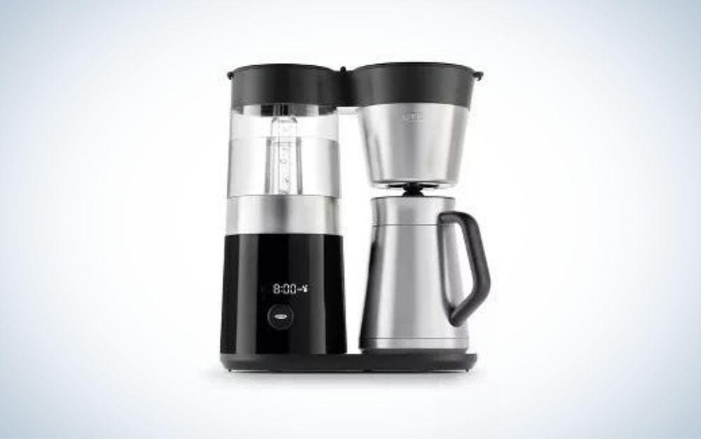 A coffee maker with two preparation utensils both black and one with a transparent plastic container on it and the other with a black lid and the whole body silver color.