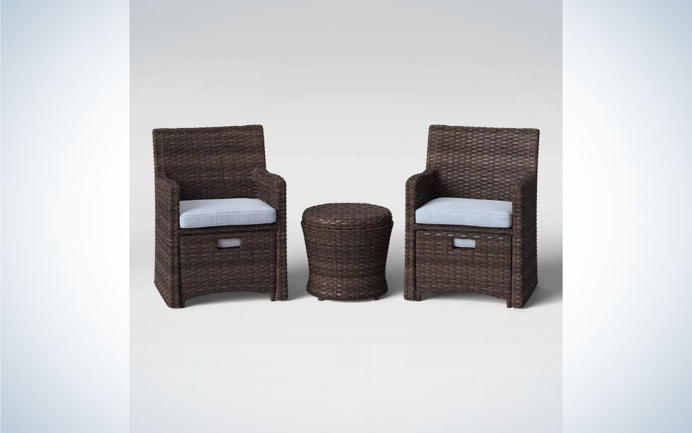Two wooden chairs and a small table between them all in dark brown, and on the chairs there are small pillows to be more comfortable.