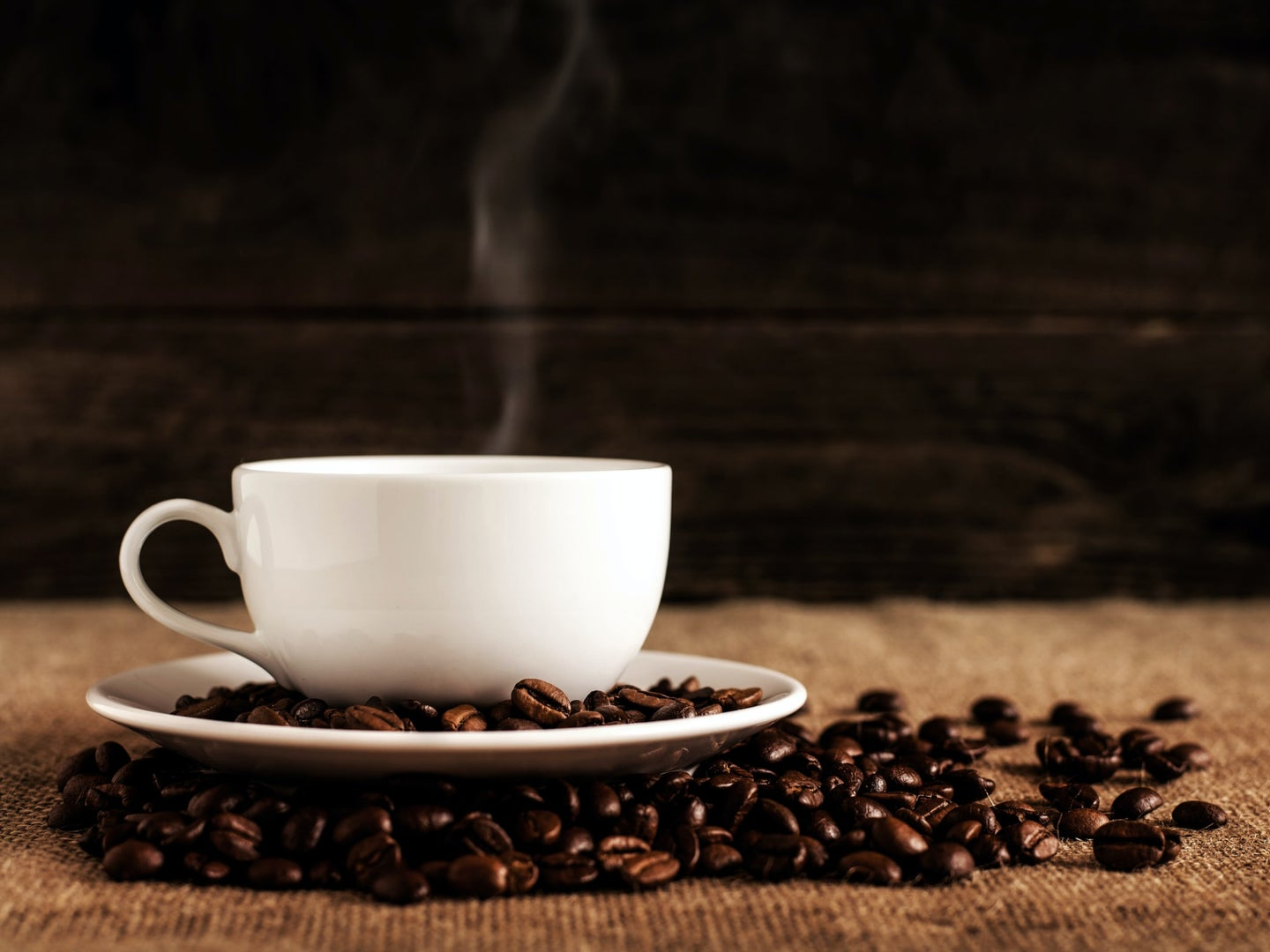 A white mug full of hot coffee on a white saucer, surrounded by roasted coffee beans.