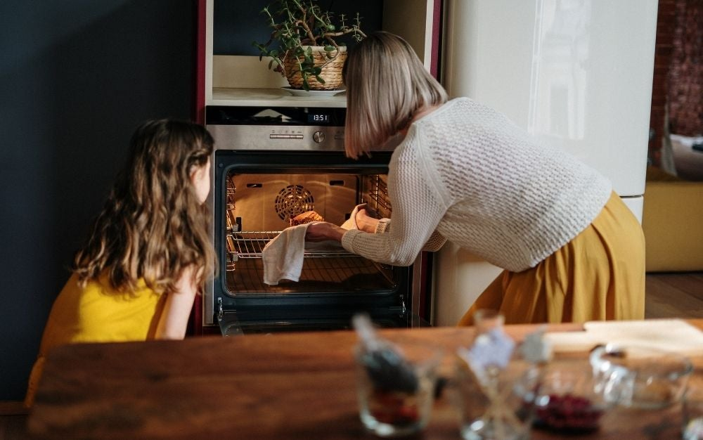 A woman with a little girl who is putting a pan in the oven with yellow light.