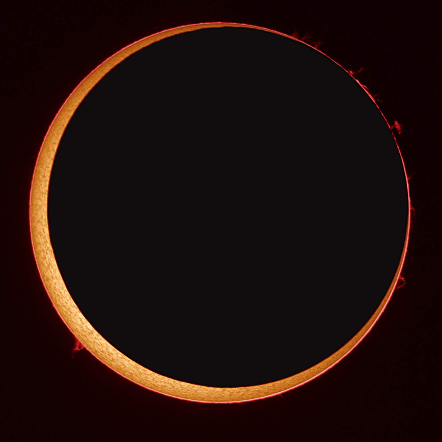 A thin ring of sun peek out behind the dark shadow of the moon.
