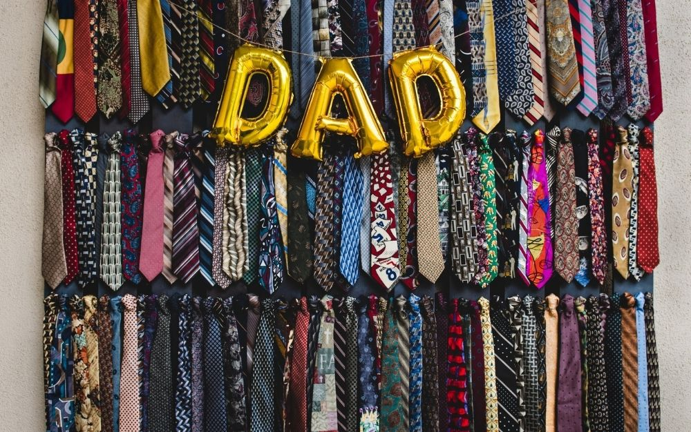 A wardrobe all with collars for men, different colors and models, as well as some balloons that write DAD.