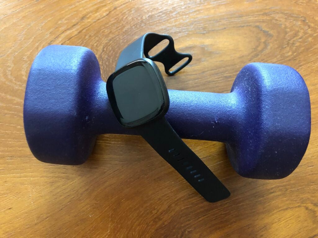 The Fitbit Versa 3 on a blue dumbbell