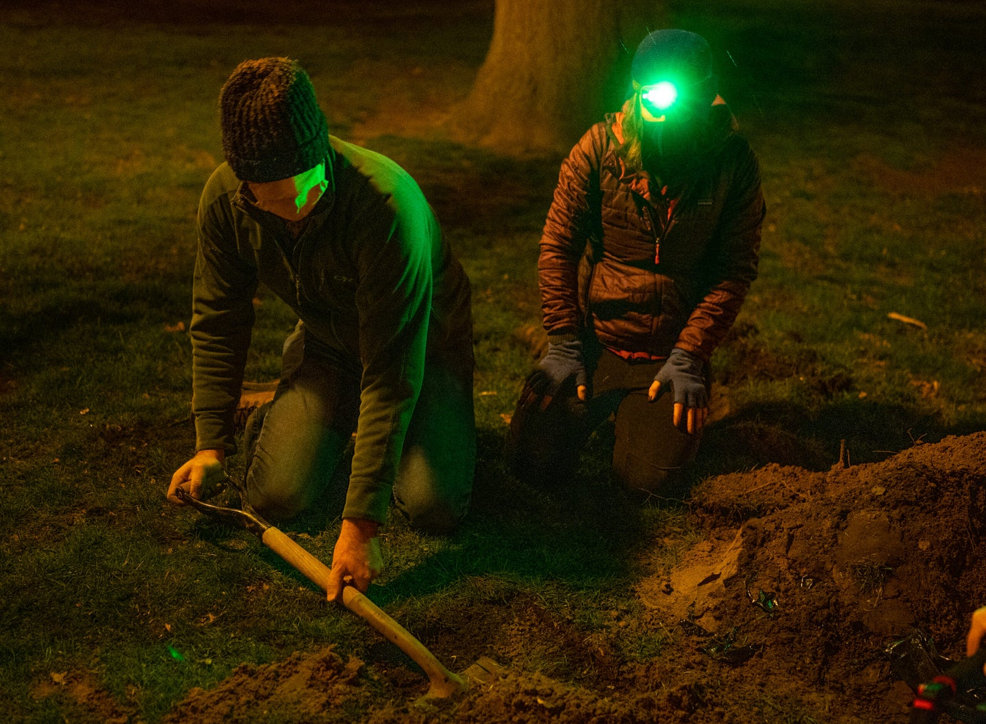 Two scientists dig with a shovel.