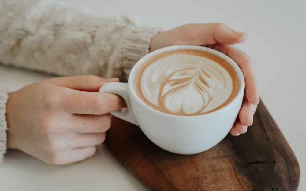 A girl with a beige sweater holding in her hands a cup of coffee with a leave formed on it.