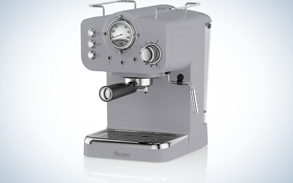 A coffee machine for making gray coffee and two compasses that indicate the level of graduation, as well as buttons attached to them at the top of the machine, as well as a black lever in the middle of it and a metal pipe for the coffee outlet.