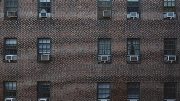 One side of a reddish-brown brick building, with 15 windows arranged in a grid on the façade, each containing a separate window air conditioning unit.
