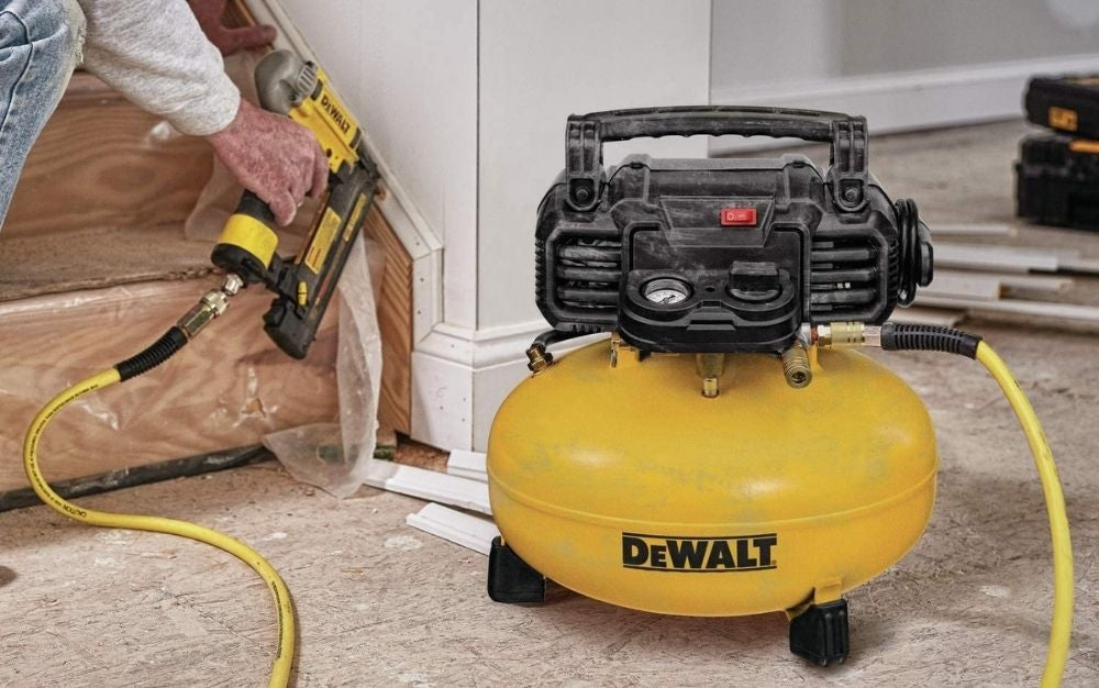 A man while repairing a yellow DEWALT electric air compressor with a round body and its engine on it and a black cable.
