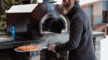 Man taking pizza out of the oven