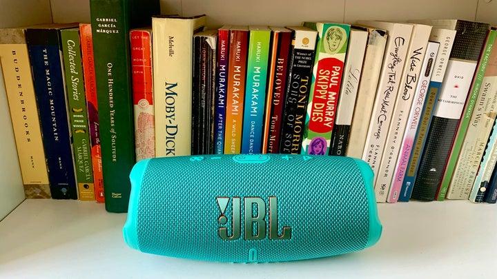 JBL Charge 5 in teal on a bookshelf