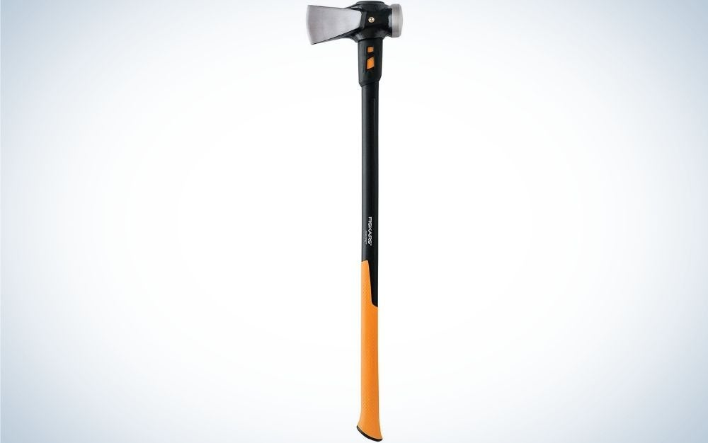 A fiskars isoCore maul with a wooden colored tail and head is a manual log splitter made of silver colored steel.
