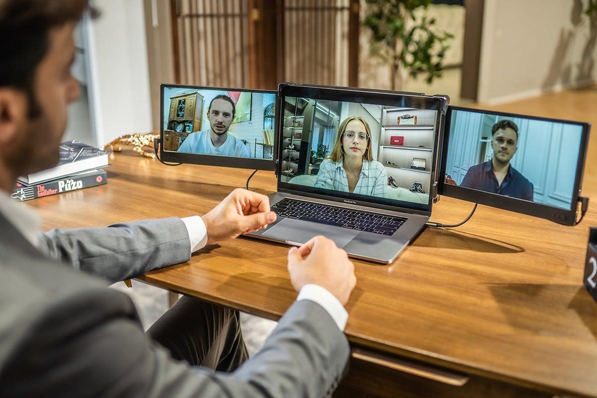 Man working at three-screen work station