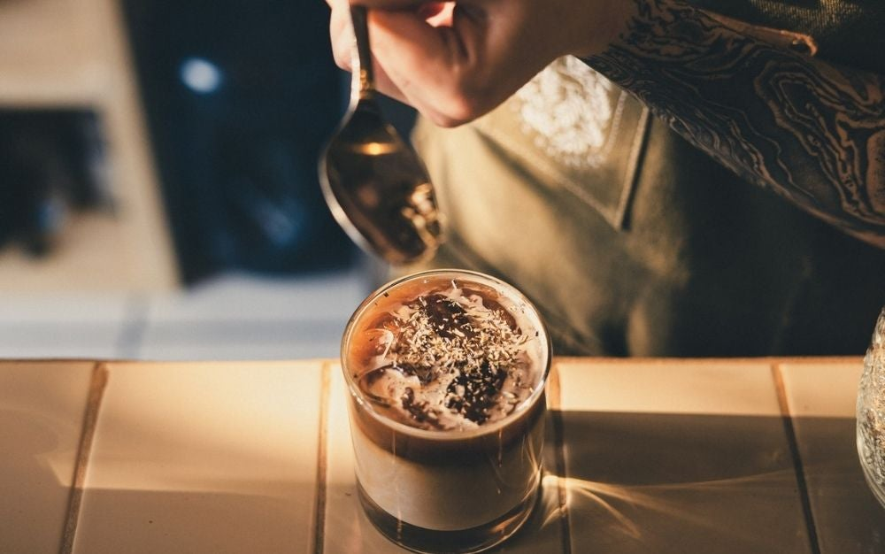 A glass of coffee and a person's hand with a silver spoon on the side of the glass as it is placed on a wooden space.