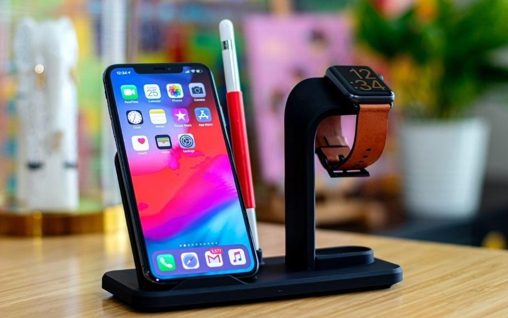 A black smartphone and a black watch standing over a rectangular shape wireless charger over a wooden table.