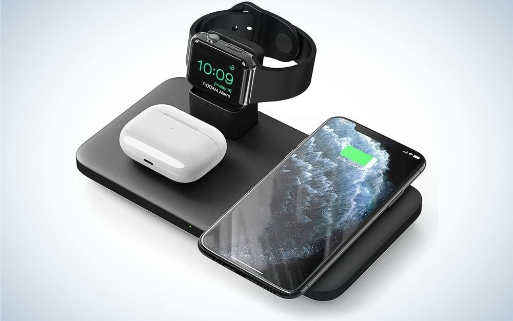 An all-black cordless phone charger as well as a watch, headphones and an Ipod placed above it.