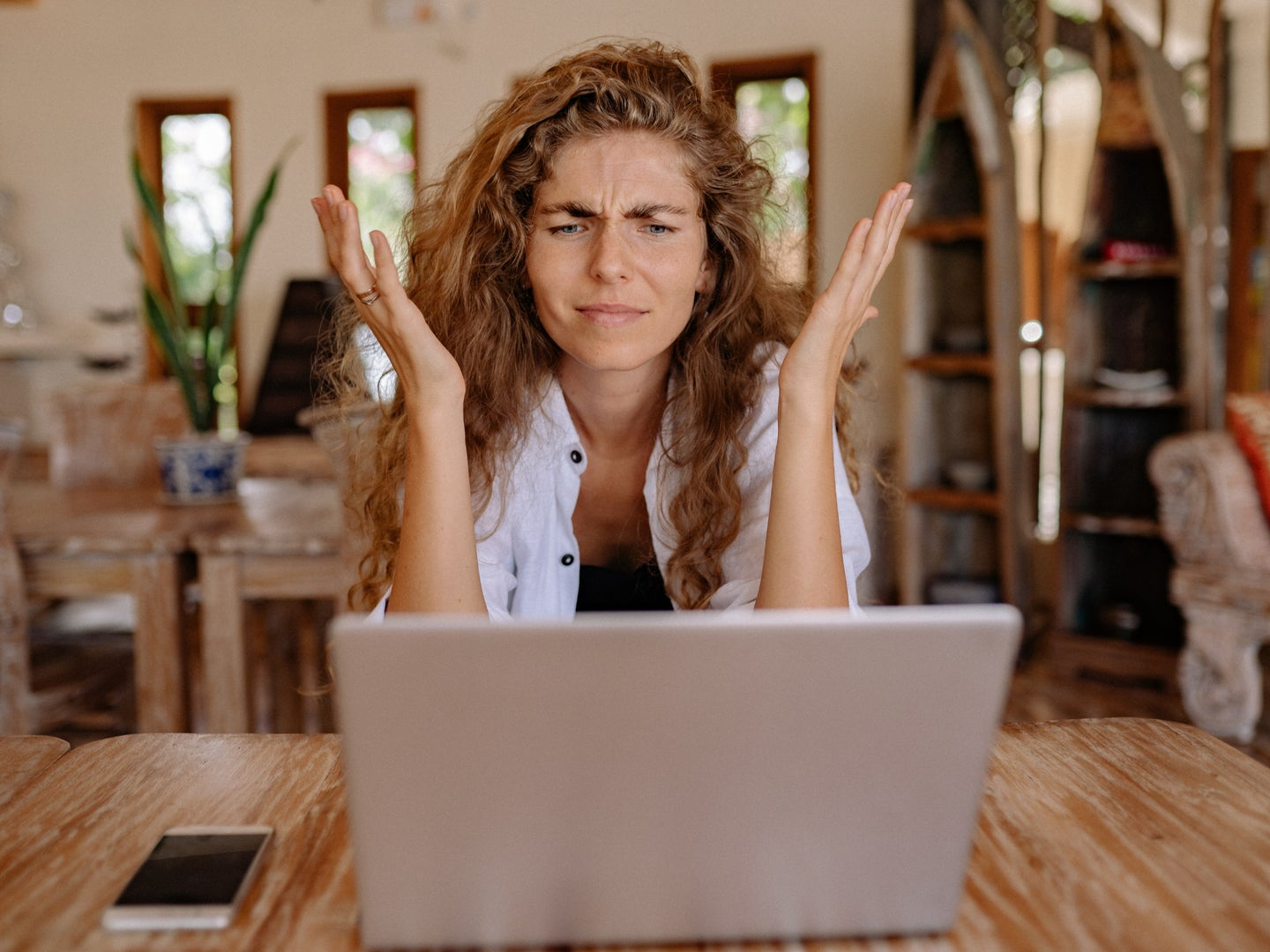 A woman with curly, dirty blonde hair sitting in front of a gray laptop with her hands in the air in an act of confusion or frustration.