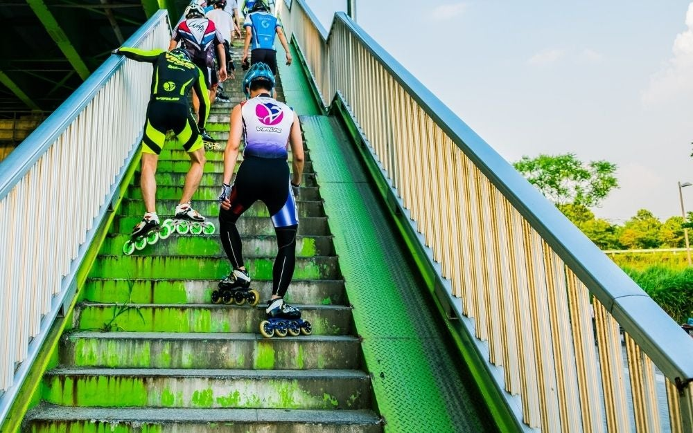 Some athletes in green sportswear as they climb the stairs wearing skates.