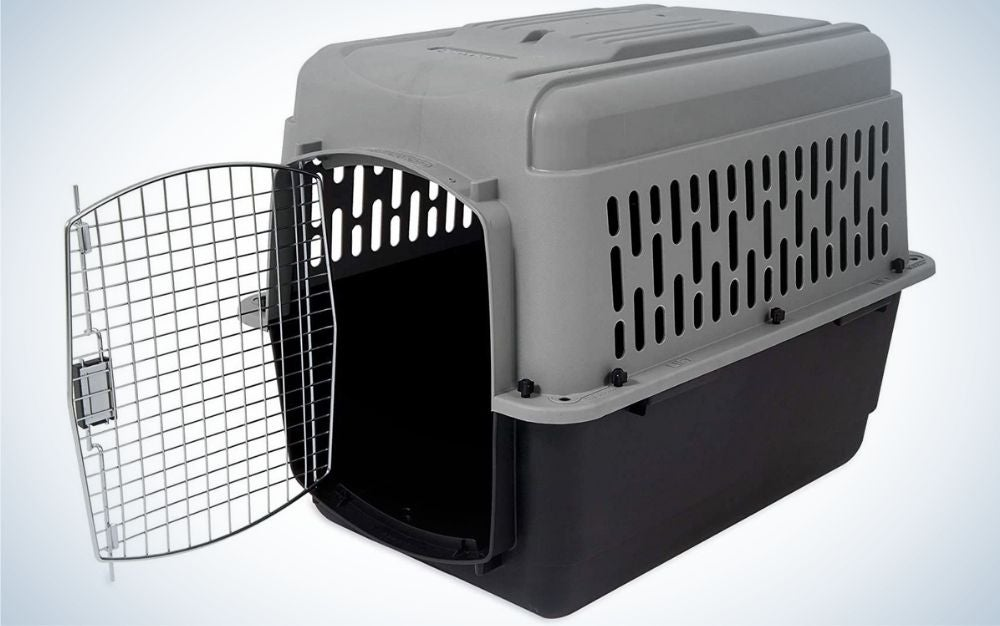 An animal cage which is made of rubber and has an open door and has black and dark gray colors.