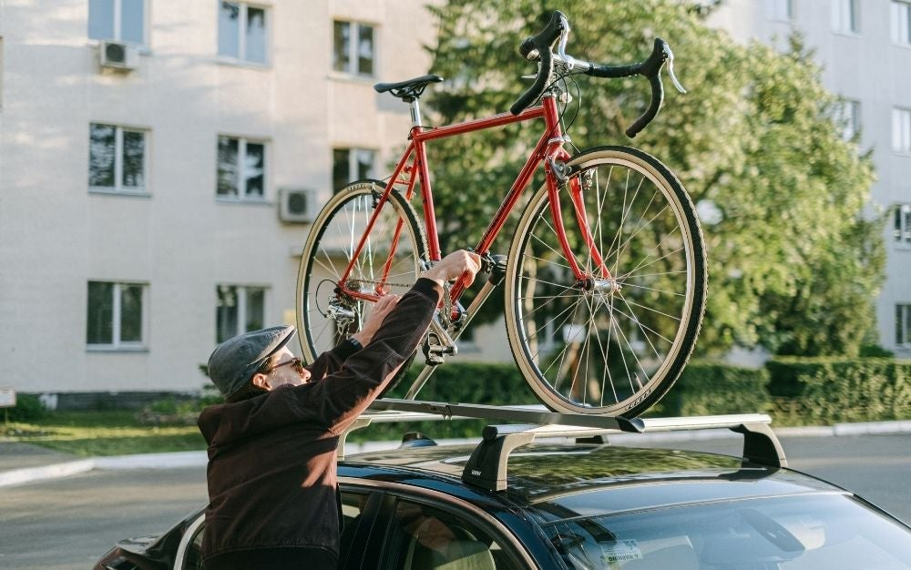 Person putting a bike on the bike racks for cars