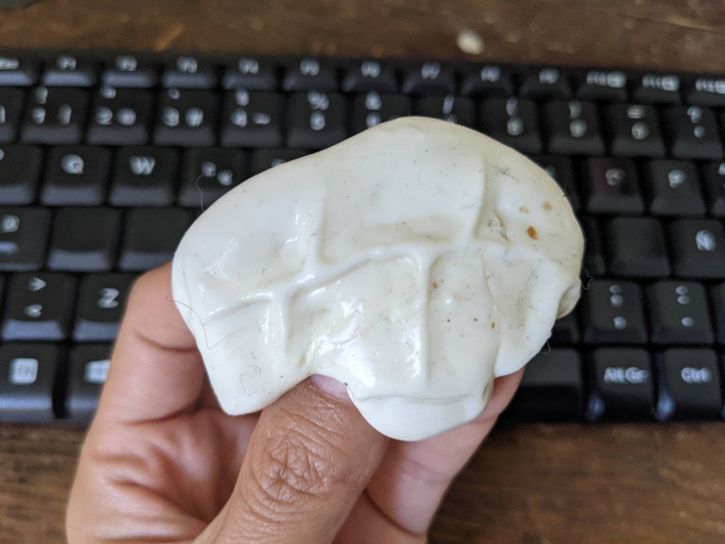 Hands holding slime with crumbs over a keyboard