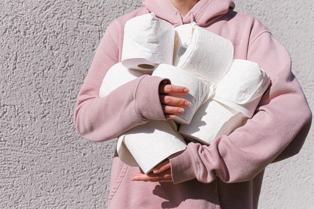 Person in pink sweatshirt holding toilet paper rolls