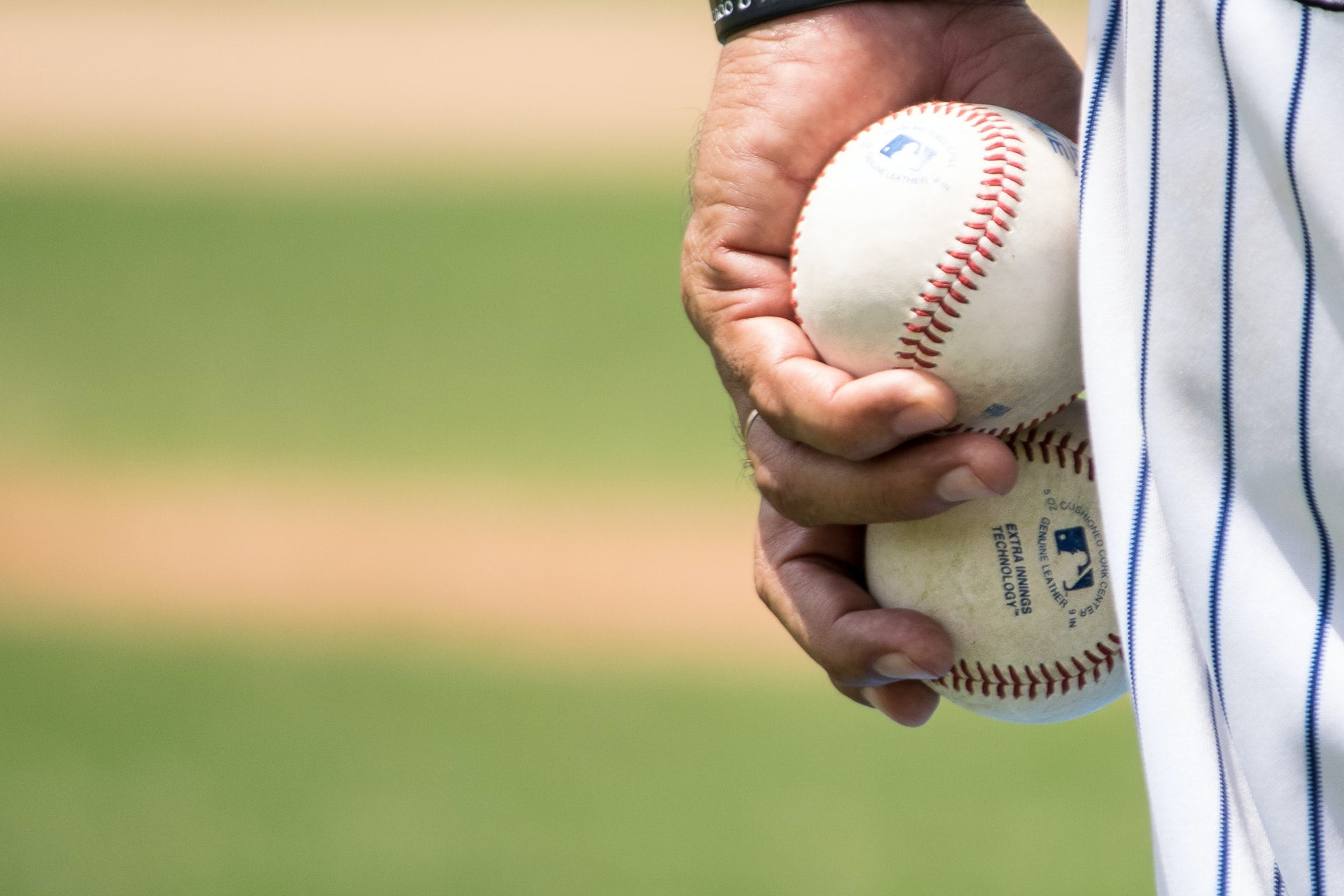 Player in pinstripes holding two baseballs