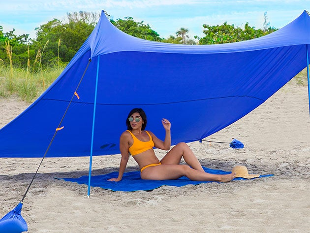Woman lounging under beach tent.