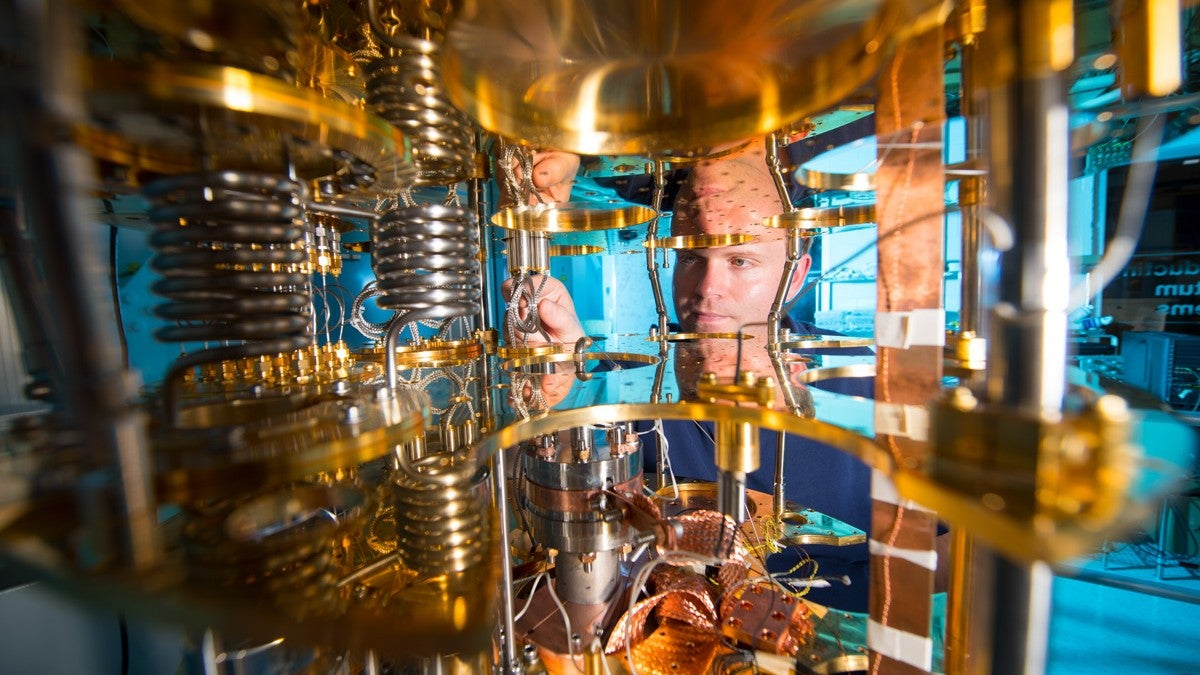 A man looks through the cooling mechanism of a quantum computer.