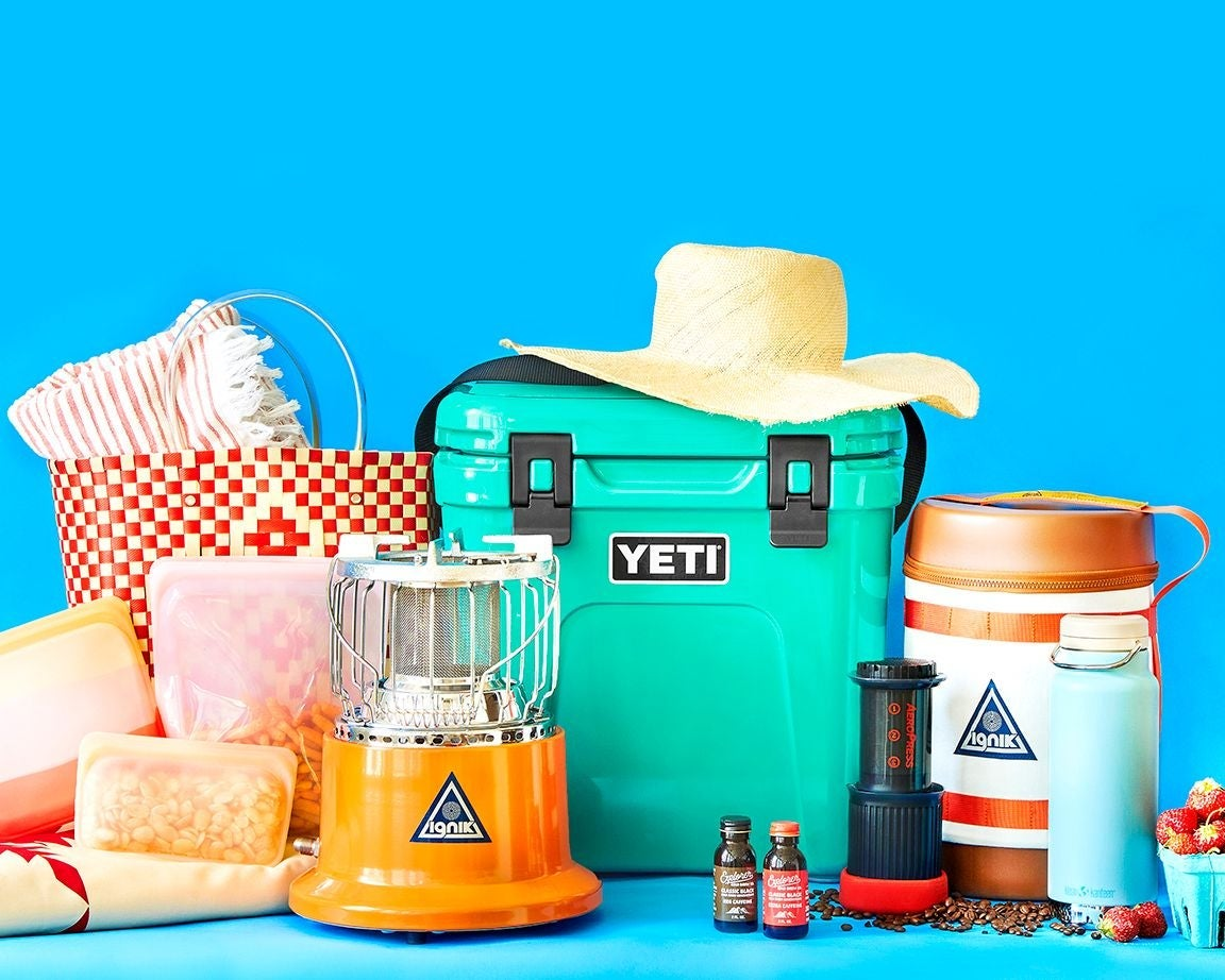 Teal Yeti cooler and other travel gear on a blue background