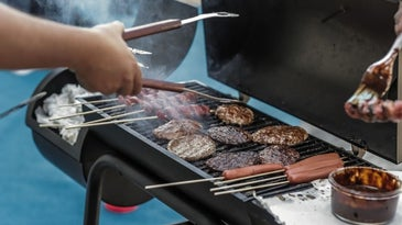 A persons hand grilling meat and sausage into a black grill with grill accessories.