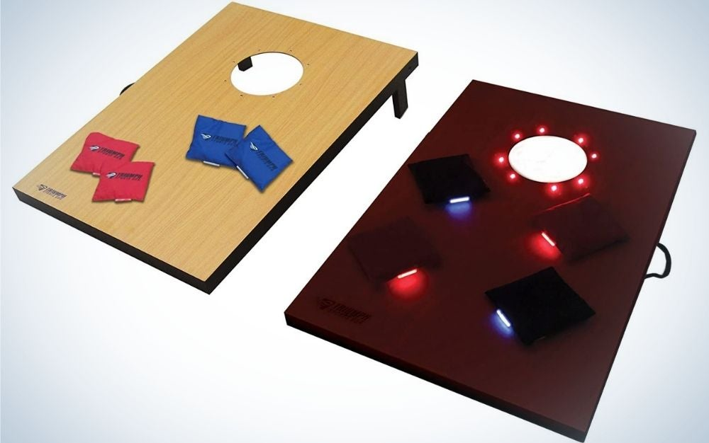 Two square shapes, one wood color and the other cherry color, both with a circular hole on top of them and between them there are blue and red pillow shapes, and on the other you can see bright lights of different colors.