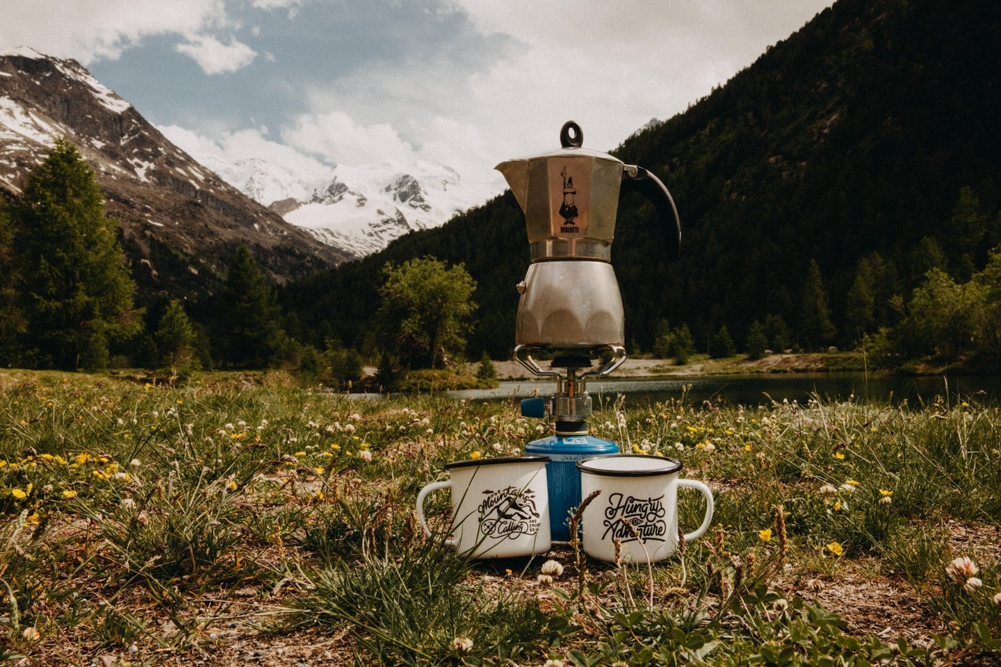 Moka pot on a burner in front of a snowy mountain with two enamel cups