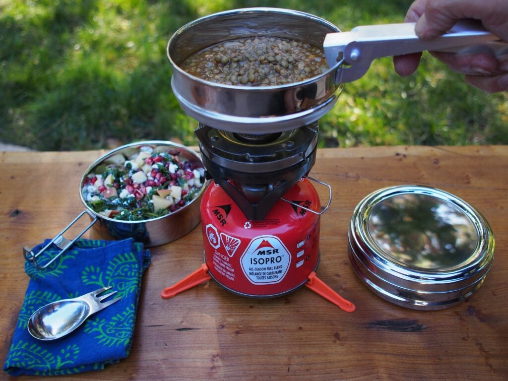 Propane burner with tin of food on a picnic bench