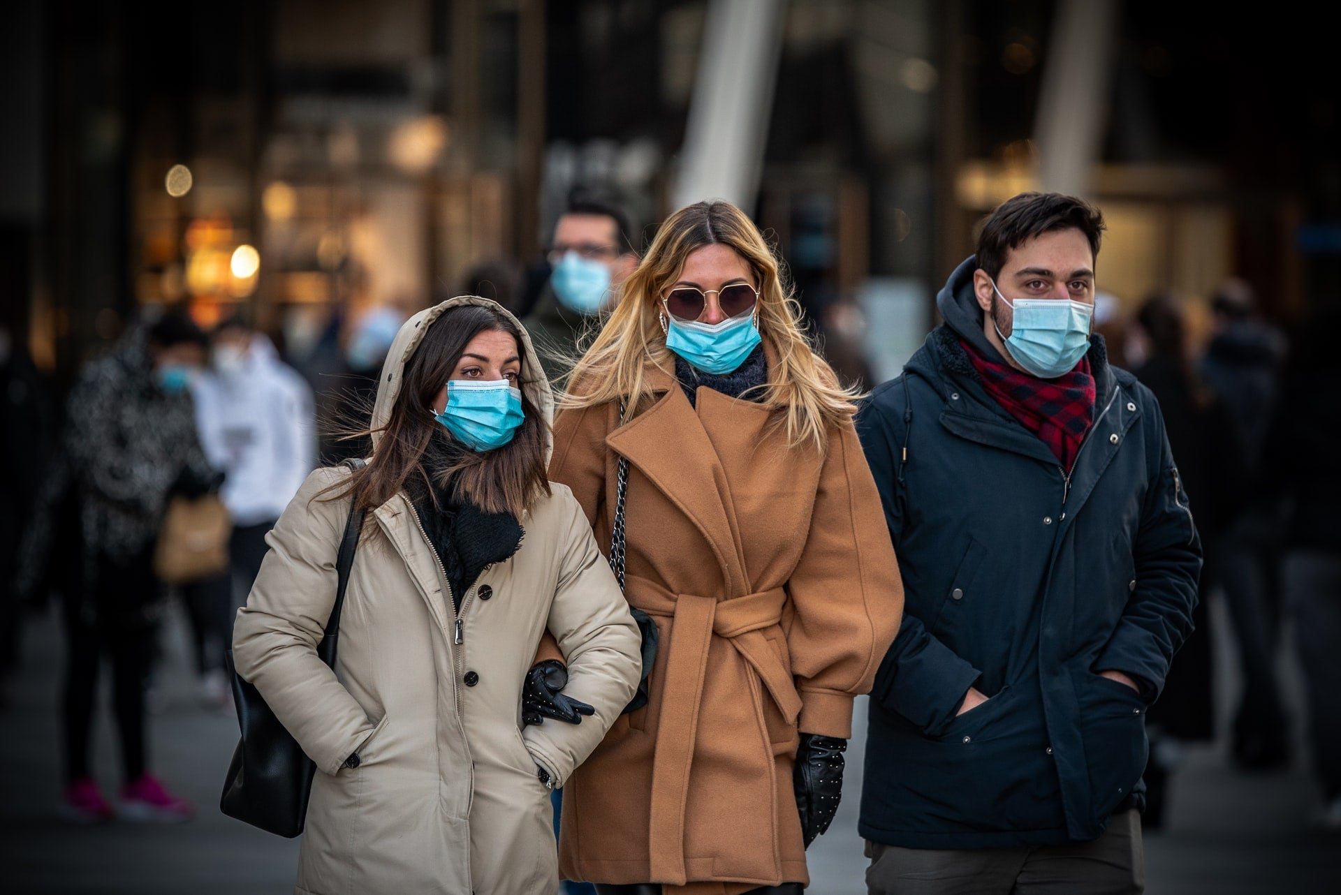 People in masks and overcoats walk through a public square.
