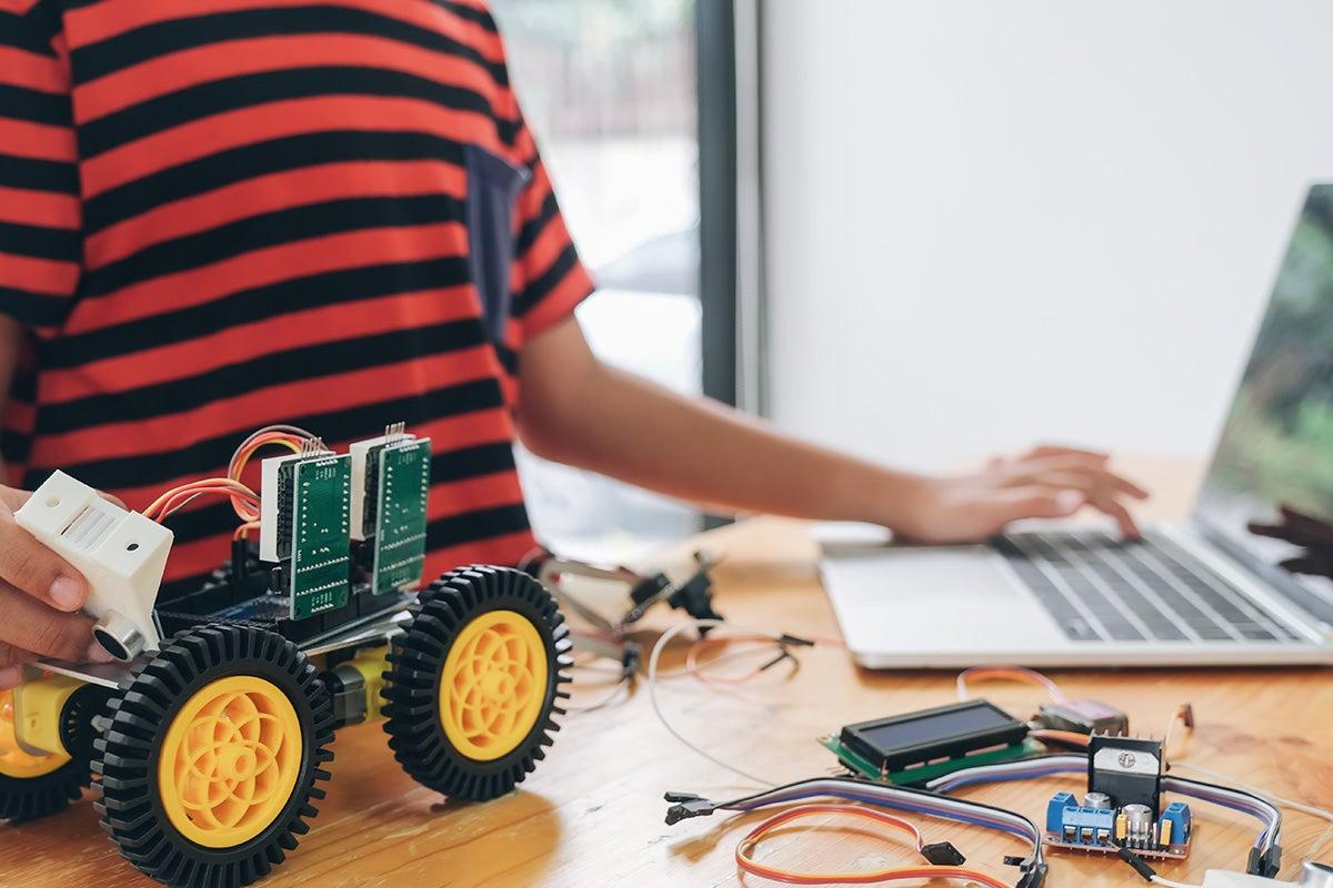 Person using laptop and robotics.