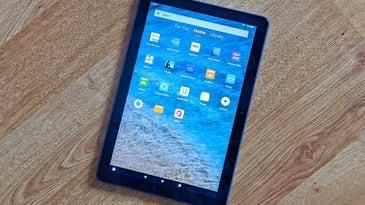 An Amazon Fire HD tablet on a wood floor.
