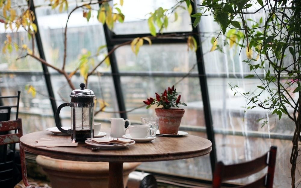 A table on a glass balcony, the table is wooden and has white coffee cups on top and a kettle to keep the coffee warm.