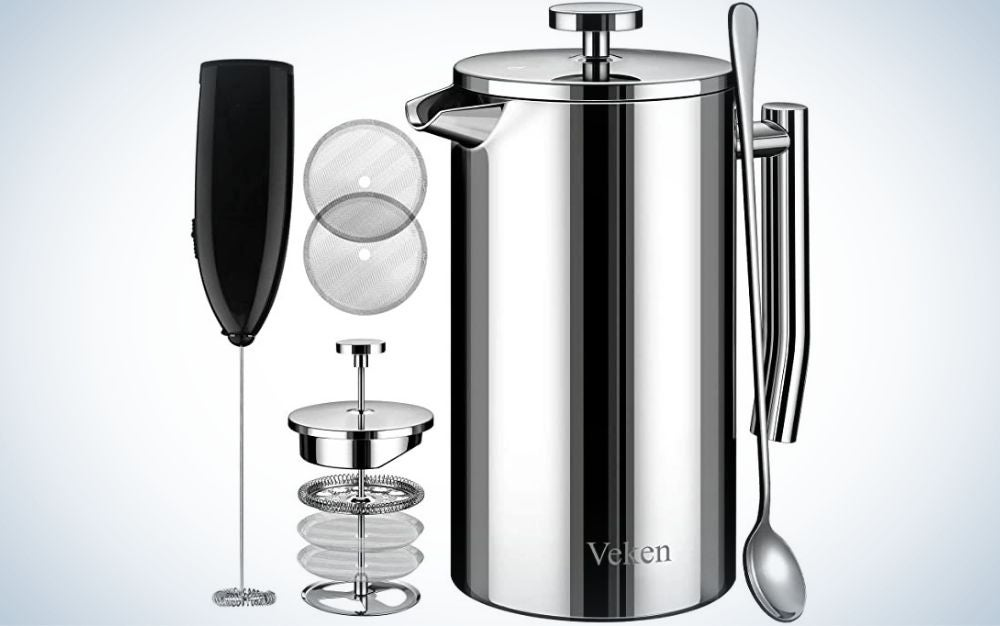 A silver kettle with a tail and lid closed from above and an apparatus with four different filters in it, as well as a black glass with a long tail and long spoons on the side of these products.