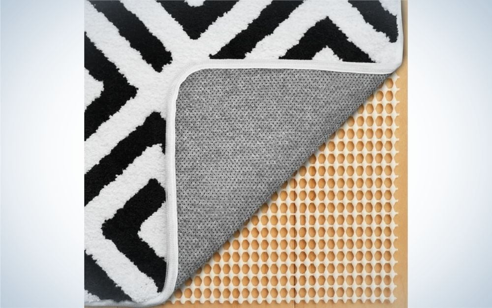 Some types of pieces on top of each other, one beige and the other on it is white with zig zag stripes black.