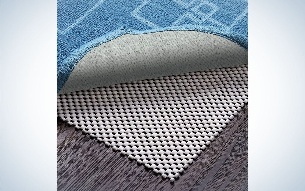 The corner of a white layer with spaces or in and under a blue carpet which are laid on a wooden parquet floor.
