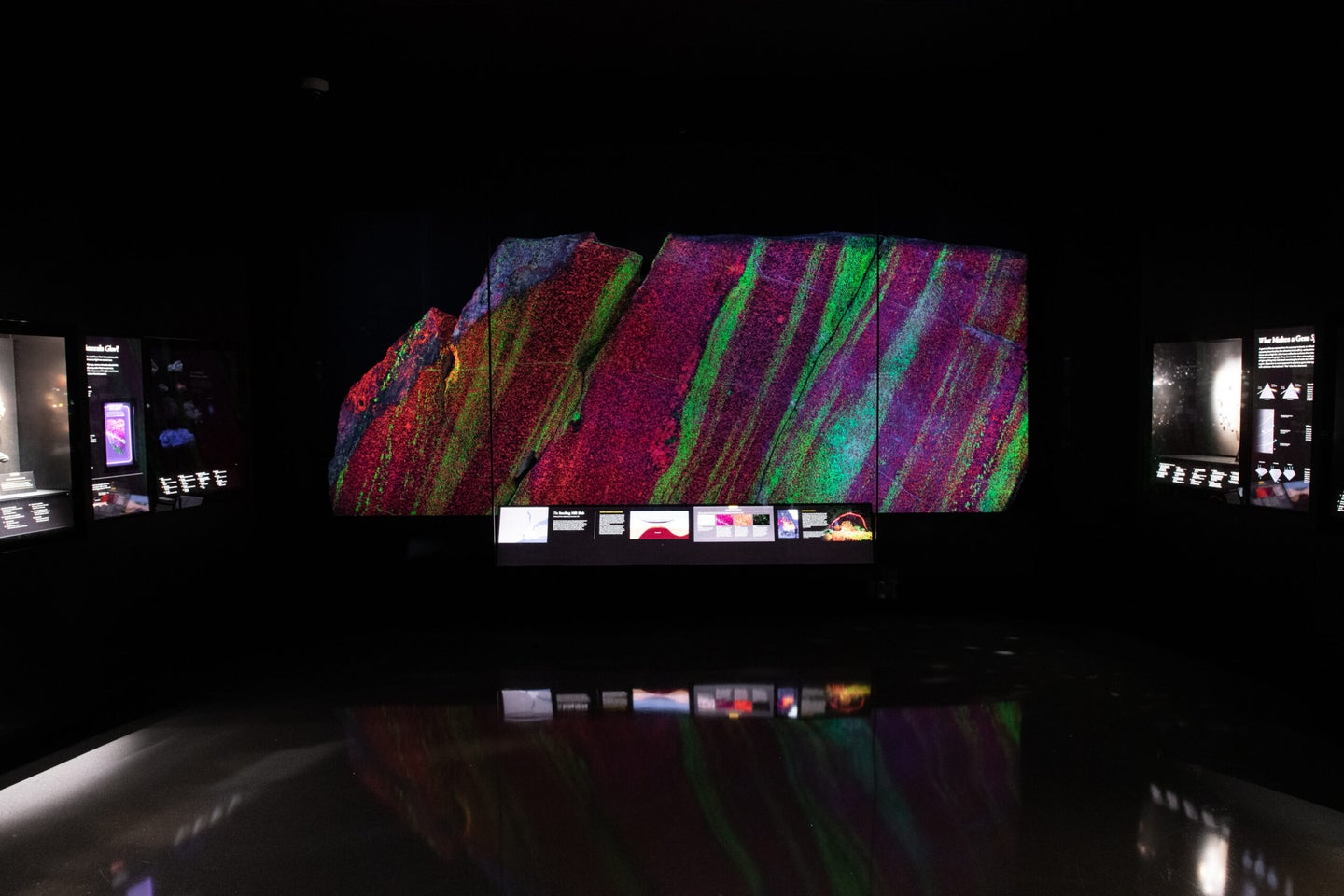 A large piece of granite rock glows in bright green and crimson red stripes behind glass and against the dark background of a museum exhibit. A few illegible, backlit display signs surround the large rock.