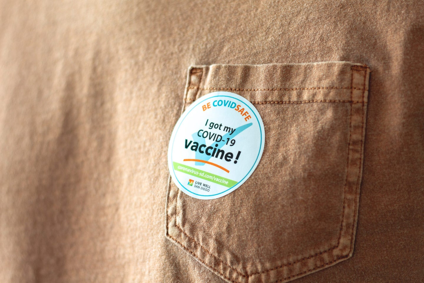 A sticker placed on the pocket of a brown tee shirt, which reads: I got my COVID-19 vaccine.