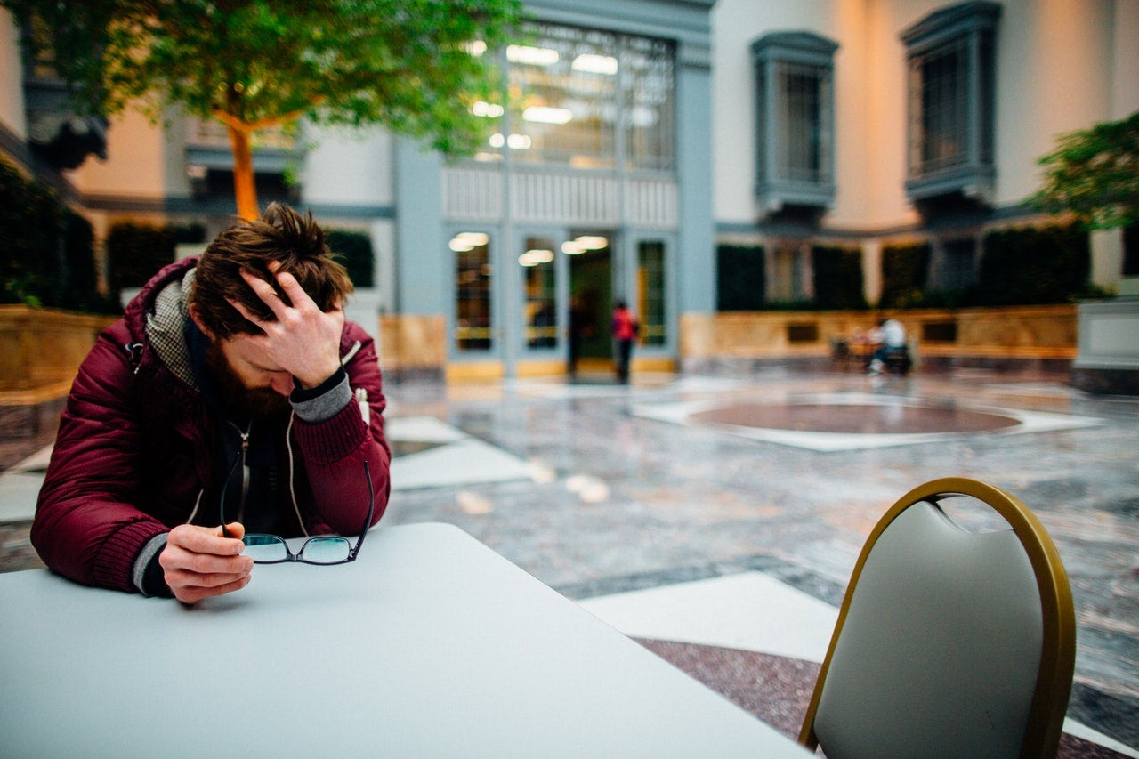 A man sits at a table with his head in his hand, looking distraught