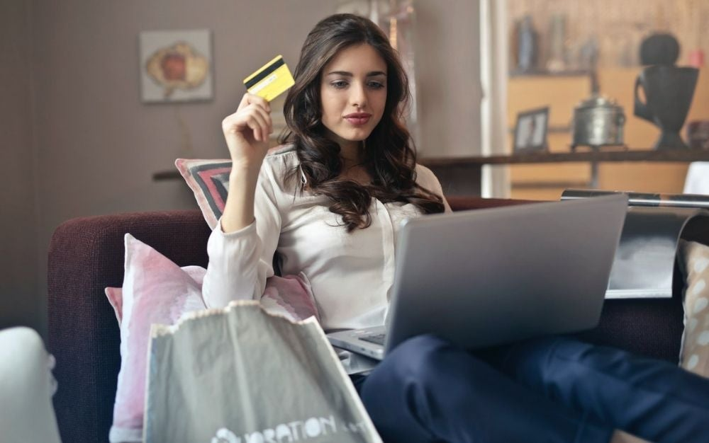 A girl with a white skirt holding in her hands a yellow card in front of her laptop.